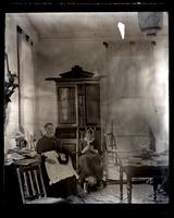 [Interior of unidentified residence, possibly Avocado, with two women on rockers doing handiwork in front of a secretary]