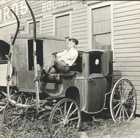[Unidentified man sitting on old coach] [graphic].