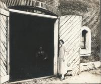 [Unidentified man and woman standing near large doorway] [graphic].
