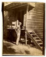 Man petting kitten near wooden house
