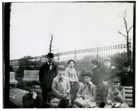 Group of children with adult male by fence and benches