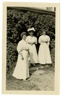 Three women in an entryway covered with ivy