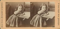 [Young girl leaning on book and chair]