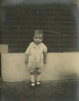 Little boy in playsuit standing in front of brick wall, Philadelphia.