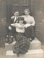 Two young women and young man on stoop, Philadelphia.
