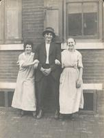 Young man and two girls standing in front of brick wall and windows, Philadelphia.