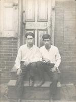 Two young men sitting on wooden stoop, Philadelphia.
