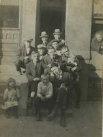 Group of men and children posing on steps of brownstone house, Philadelphia.