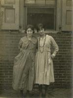 Two young women standing in front of open window of brick house, Philadelphia.