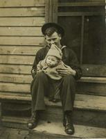 Young man in sailor uniform holding infant on wooden stoop, Philadelphia.