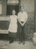 Man and woman standing in front of a brick house, Philadelphia.