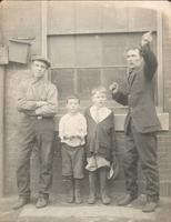 Two men and two boys in front of factory window, Philadelphia.