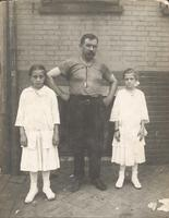 Man standing with two girls in front of brick wall, Philadelphia.
