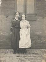 Two young women in front of brick wall and shutters, Philadelphia.