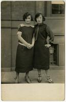 Two nicely dressed young women standing in front of brick building, Philadelphia.