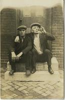 Two workmen sitting on a stoop, one drinking out of a beer bottle, Philadelphia.