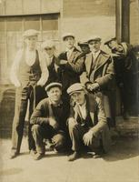 Eight men and boys standing outside a brick building, Philadelphia.