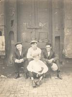Four men sitting in front of large doorway, Philadelphia.