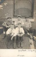Five boys sitting on the wooden door of a sidewalk cellar entrance, Philadelphia.