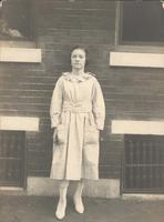 Young woman standing in front of brick wall and windows, Philadelphia.