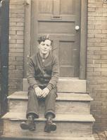 Young man in cardigan sweater sitting on wooden stoop, Philadelphia.