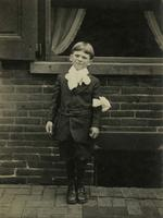 Boy wearing a suit and ribbon bow on arm standing in front of brick house, Philadelphia.