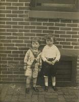 Two little boys in front of brick house, Philadelphia.