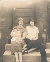 Two women with infant sitting on stoop, Philadelphia.