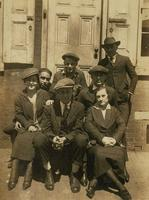 Five men and two women on the front steps of a brick house, Philadelphia.