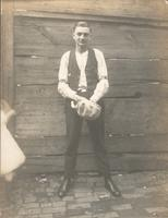 Young man standing in front of board fence, Philadelphia.