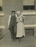 Young man and woman standing in front of a brick house, Philadelphia.