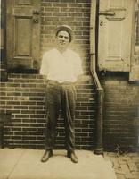 Man in straw bowler standing in front of brick house, Philadelphia.