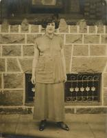 Woman standing in front of brick house with stone porch, Philadelphia.