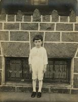 Little boy with frilly shirt standing in front of a stone porch, Philadelphia.