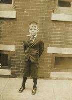 Little boy in suit standing in front of a brick house, Philadelphia.