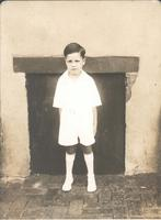 Boy wearing white outfit standing in front of wall, Philadelphia.