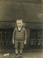 Little boy wearing printed sweater standing in front of brownstone house, Philadelphia.