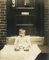 Small child sitting on a blanket on a wooden step, Philadelphia.