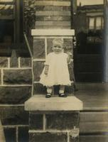 Small child standing on a stone porch, Philadelphia.
