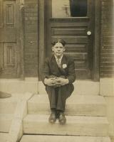 Young man in suit sitting on marble steps, Philadelphia.