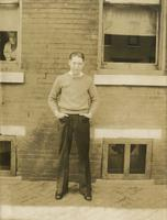 Young man in sweater standing in front of brick house, Philadelphia.