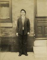 Young man in suit standing in front of brick house, Philadelphia.
