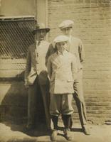 Boy and two young men in suits standing outside brick building, Philadelphia.