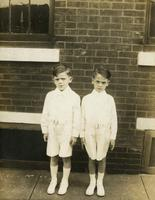 Two little boys dressed for First Communion standing in front of a brick house, Philadelphia.