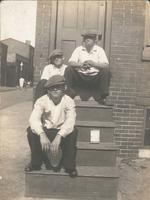 Three boys in caps sitting on wooden steps, Philadelphia.