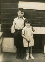 Boy and girl standing in front of brick house, Philadelphia.