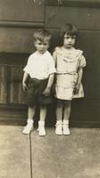 Boy and girl standing in front of brownstone house, Philadelphia.