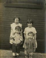 Two boys and two girls posing outside brick house, Philadelphia.