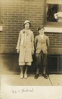 Teenage girl and younger boy standing in front of brick house, Philadelphia.