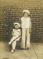 Boy and girl posing in sailor outfits in front of brick wall, Philadelphia.